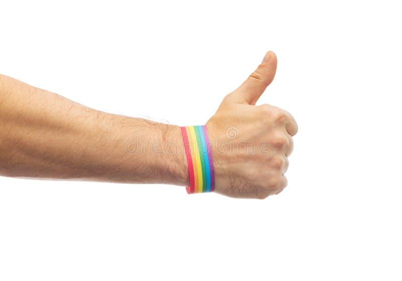 La mano con pulsera del arco iris del orgullo gay muestra el pulgar imagenes de archivo