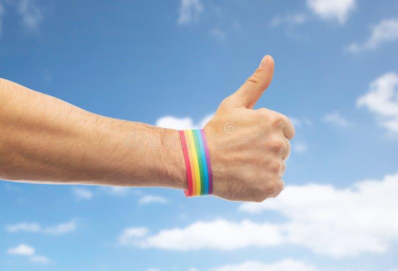 La mano con pulsera del arco iris del orgullo gay muestra el pulgar fotografía de archivo libre de regalías
