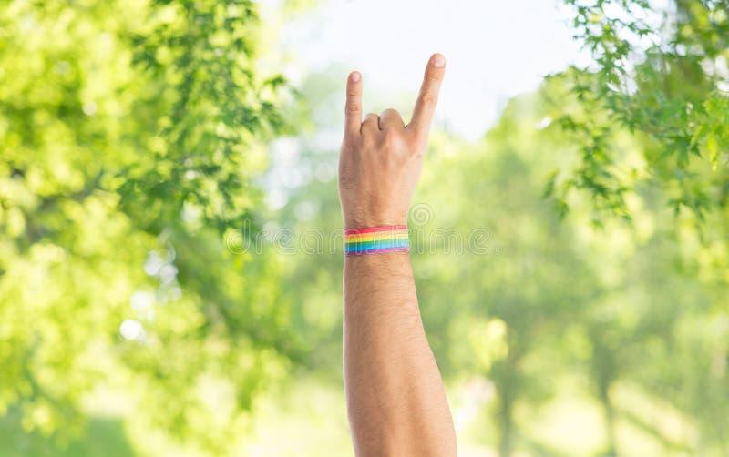 La mano con pulsera del arco iris del orgullo gay muestra la roca imagen de archivo