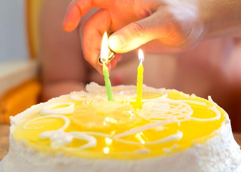 La mano con un encendedor enciende velas en la torta en el cumpleaños imagen de archivo
