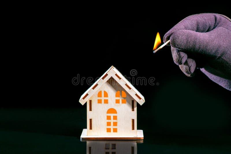 La mano con un partido ardiente fija el fuego al modelo de la casa en fondo negro imagen de archivo libre de regalías