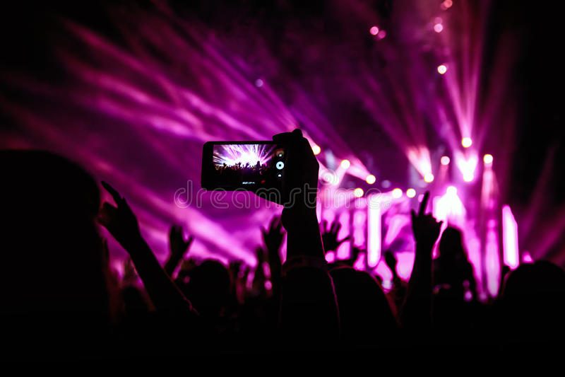 La mano con uno smartphone registra il festival di musica in diretta, prendente la foto della fase di concerto fotografia stock
