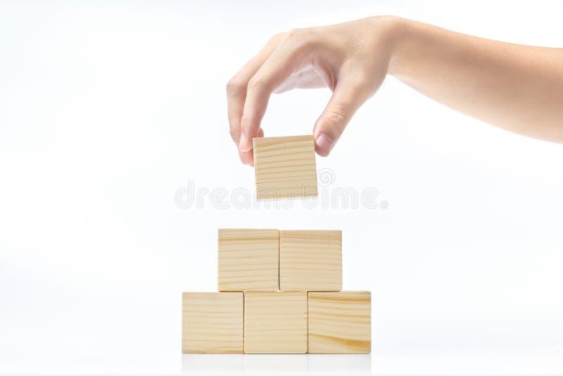 La mano construye una pirámide de un bloque de madera fotografía de archivo