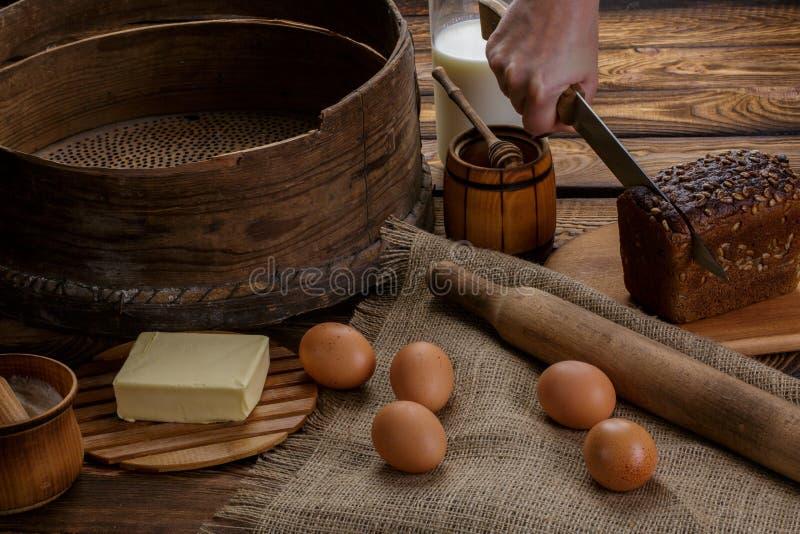 La mano corta el pan negro en el fondo de los ingredientes para cocinar el pan foto de archivo