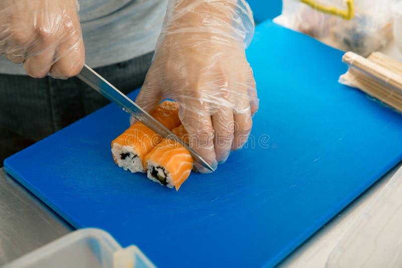 La mano corta el primer del rollo en una tabla de cortar el cocinero prepara el sushi en un restaurante japonés fotografía de archivo libre de regalías
