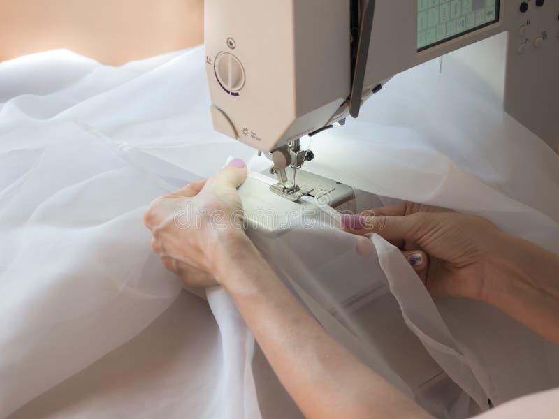La mano cose una Tulle en la m?quina de coser imágenes de archivo libres de regalías