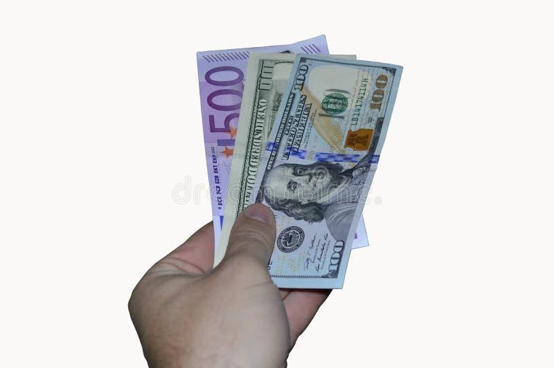 La mano da cientos billetes de banco del dólar y del euro en un fondo blanco imagen de archivo