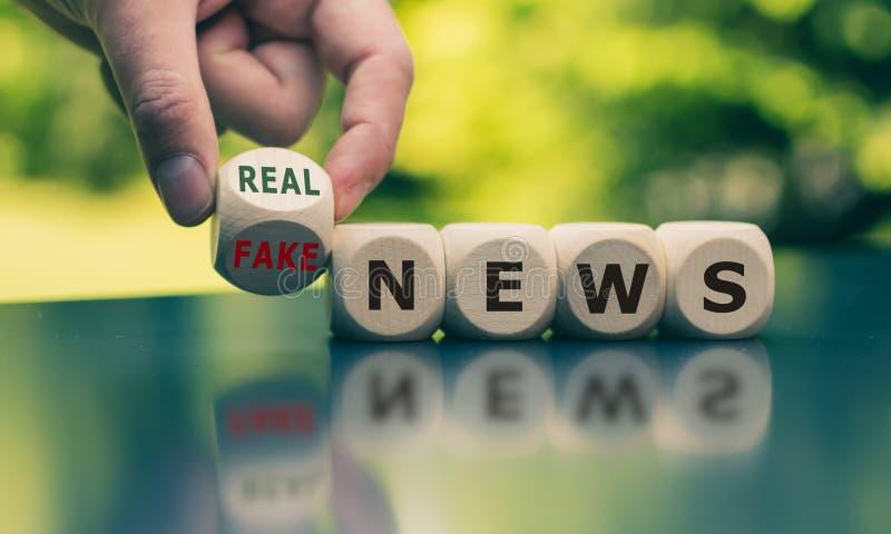 La mano da vuelta a un cubo y cambia las noticias falsas de la expresión ''a las noticias reales ' fotografía de archivo libre de regalías