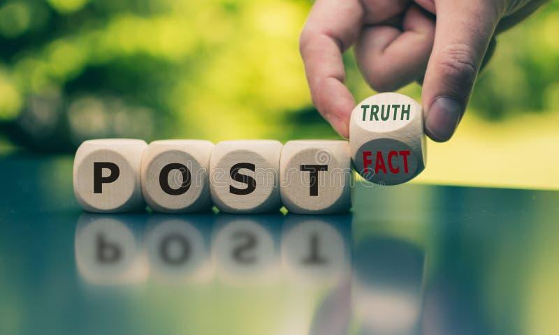La mano da vuelta a un cubo y cambia verdad del poste 'hecho 'del poste la 'de la expresión del ' imagenes de archivo