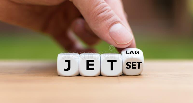 La mano da vuelta a un dado y cambia la palabra 'jet lag 'al 'jet set ' fotos de archivo