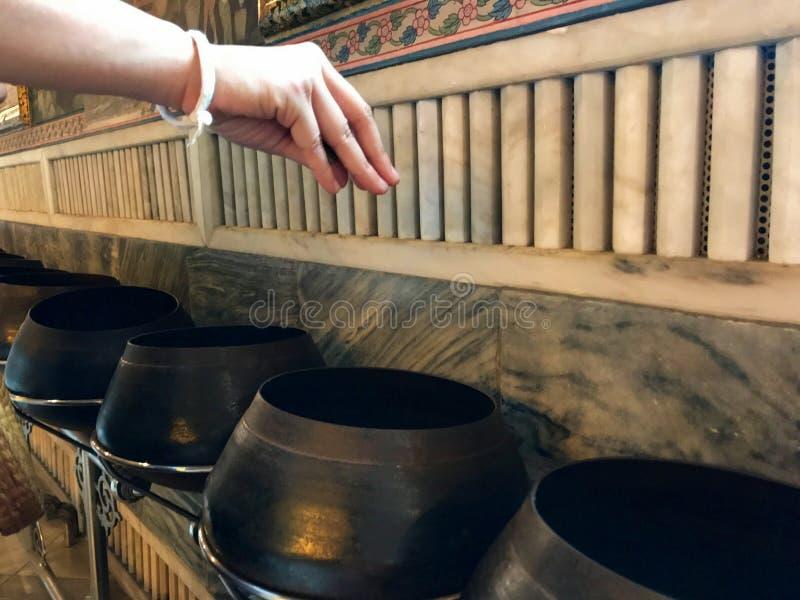 La mano de la donación en templo budista fotos de archivo libres de regalías