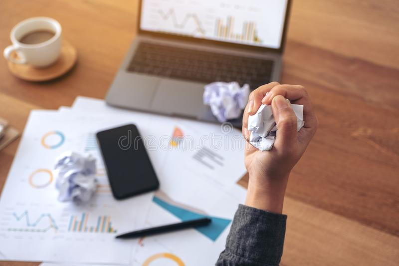 La mano de la empresaria estropeó los papeles con el ordenador portátil y el teléfono móvil en la tabla en oficina imagen de archivo libre de regalías