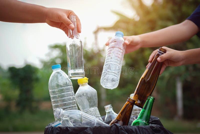 la mano de la gente que sostiene el plástico de la botella de la basura y el vidrio que pone en reciclan el bolso imagen de archivo