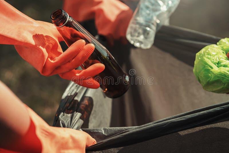 la mano de la gente que sostiene el pl?stico de la botella de la basura y el vidrio que pone en reciclan el bolso para limpiar fotos de archivo libres de regalías