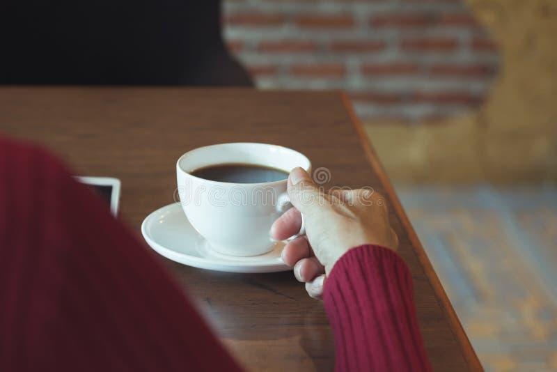 La mano de la hembra que sostiene una taza de café en la tabla de madera fotos de archivo