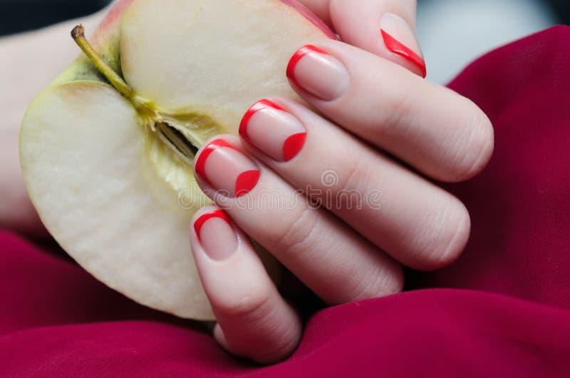 La mano de la mujer con la manicura francesa roja imagenes de archivo