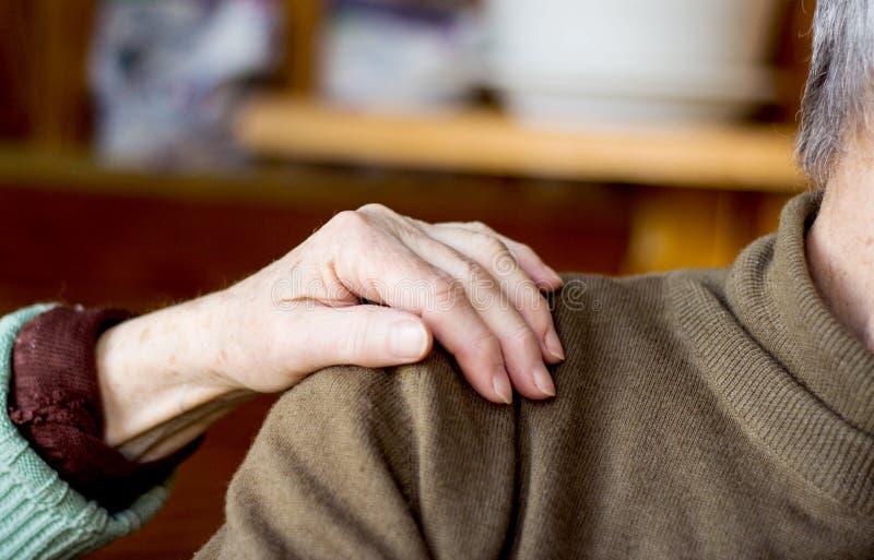 La mano de la mujer en el hombro del hombre imagen de archivo libre de regalías