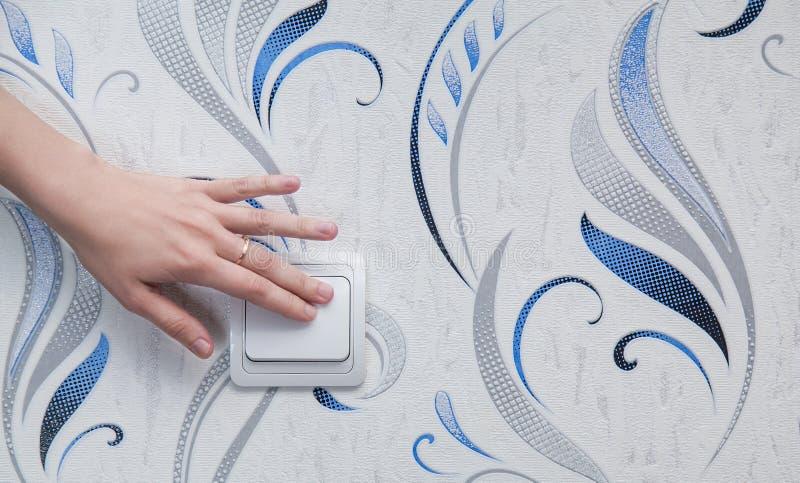 La mano de la mujer enciende las luces foto de archivo libre de regalías