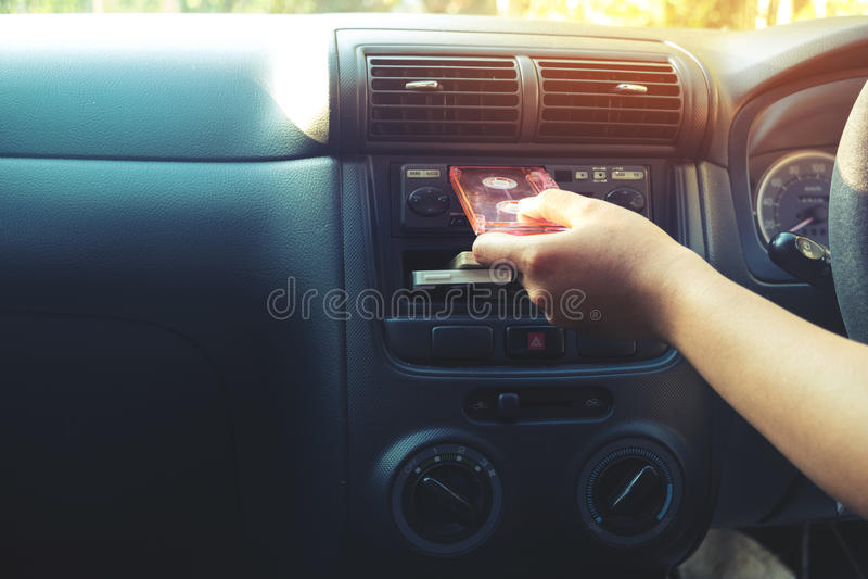 La mano de la mujer que sostiene el casete de cinta en el coche para conducir escucha música fotos de archivo libres de regalías