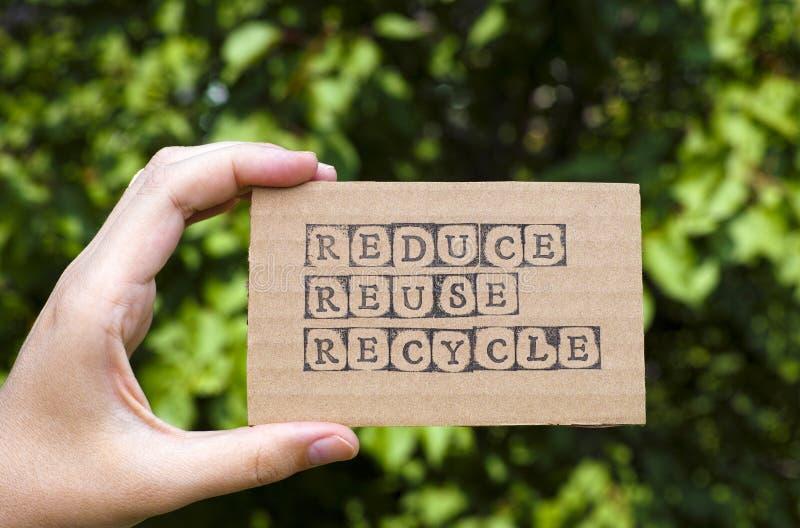 La mano de la mujer que sostiene la tarjeta de la cartulina con palabras reduce la reutilización Recycl foto de archivo