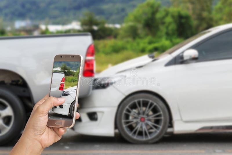 La mano de la mujer que sostiene smartphone y toma la foto del accidente de tráfico imagen de archivo