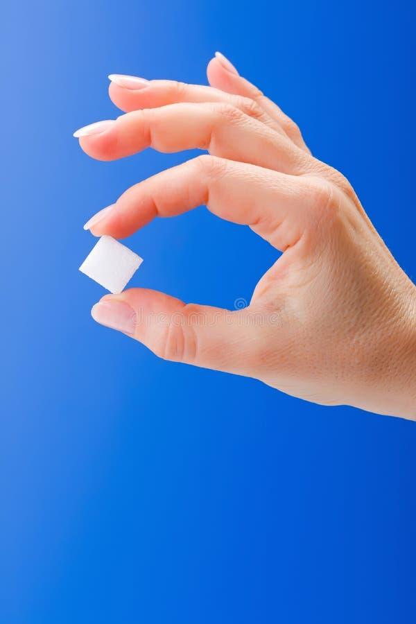 La mano de la mujer que sostiene un cubo del azúcar blanco fotografía de archivo