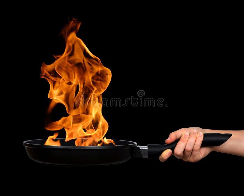 La mano de la mujer que sostiene un sartén con las llamas foto de archivo