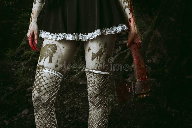 La mano de la mujer sucia que sostiene un hacha sangrienta imagen de archivo
