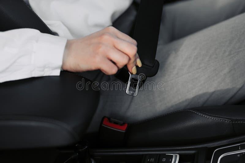 La mano de las mujeres sujeta el cintur?n de seguridad del coche Cierre su correa del asiento de carro mientras que se sienta den imagenes de archivo