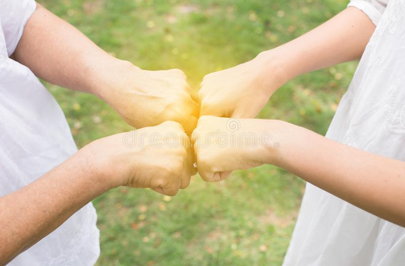 La mano de los ancianos femeninos asiáticos que dan el topetón del puño a las mujeres jovenes de las manos en al aire libre, se c foto de archivo libre de regalías