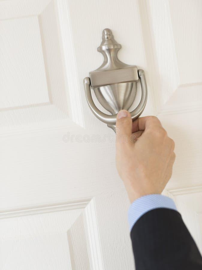 La mano de los hombres de negocios que golpea el tirador de puerta imágenes de archivo libres de regalías