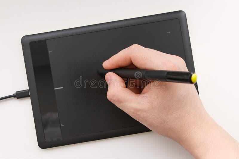 La mano de los hombres dibuja en una tableta de gráficos usando una aguja fotografía de archivo