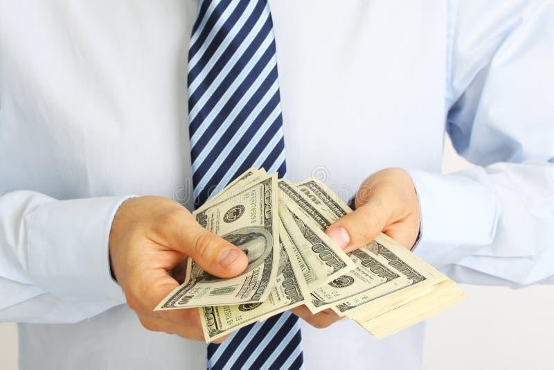 La mano de los hombres que lleva a cabo billetes de dólar del americano ciento del dinero Mano del dinero de ofrecimiento del hom imágenes de archivo libres de regalías