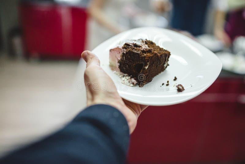 la mano de los hombres que lleva a cabo la rebanada de pastel de bodas esmaltado del chocolate en la placa foto de archivo