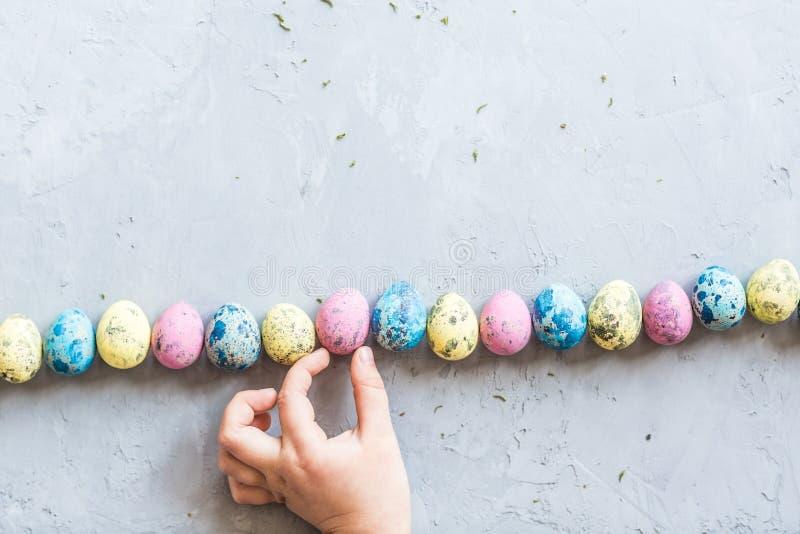 La mano de los niños que sostiene los huevos de Pascua coloridos que mienten en fondo concreto gris Endecha plana Visión superior fotos de archivo