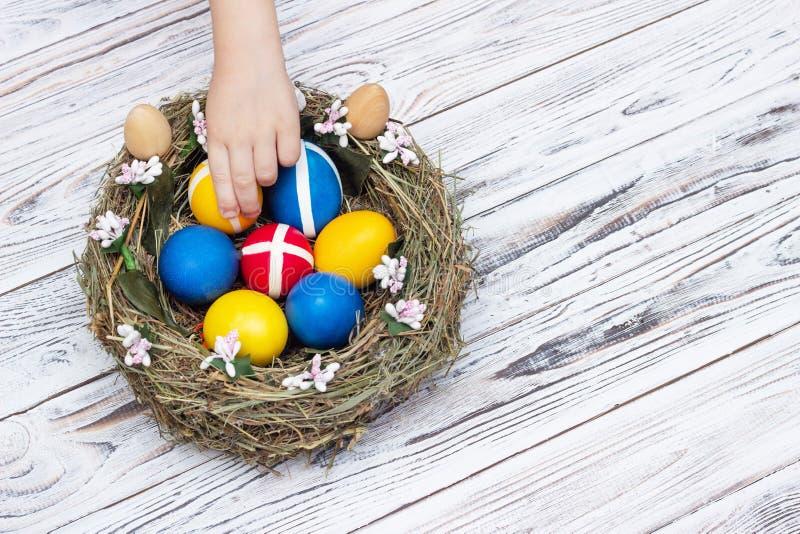 La mano de los niños toma los huevos de Pascua coloreados de una jerarquía en un fondo de madera blanco, día de fiesta de Pascua, fotos de archivo