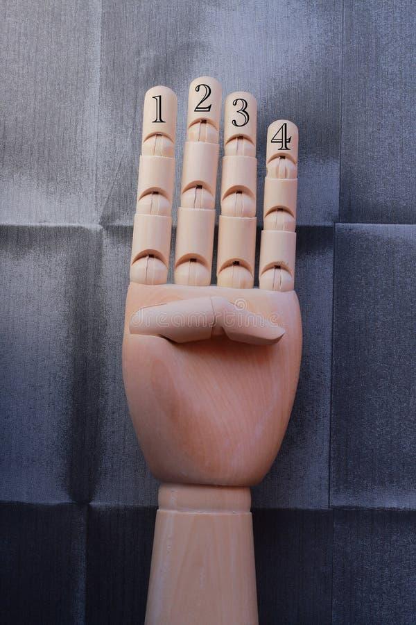 La mano de madera con cuatro fingeres aumentó y numeró con números uno, dos, tres y cuatro fotos de archivo