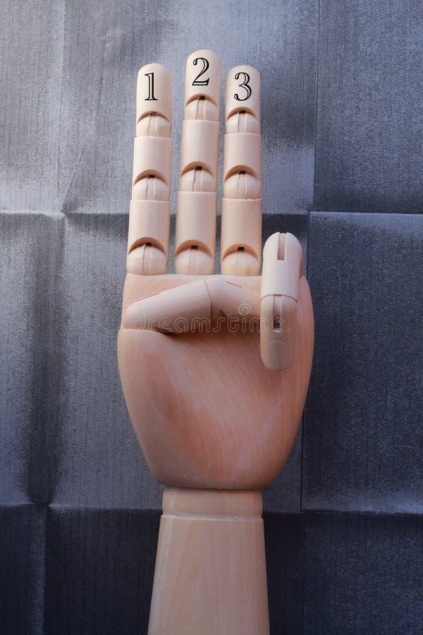 La mano de madera con tres fingeres aumentó y numeró con números uno, dos y tres foto de archivo