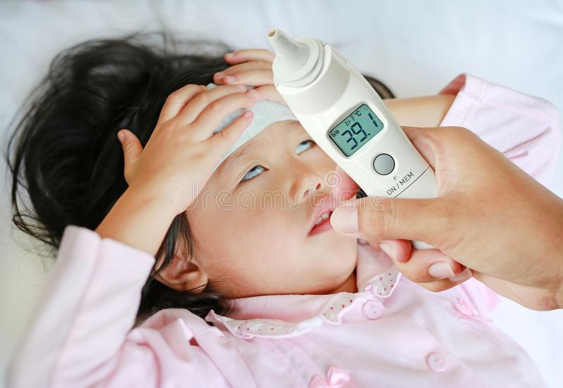 La mano de la madre del primer toma la temperatura para su hija con la alta presión del termómetro de oído en cama en casa imagen de archivo libre de regalías