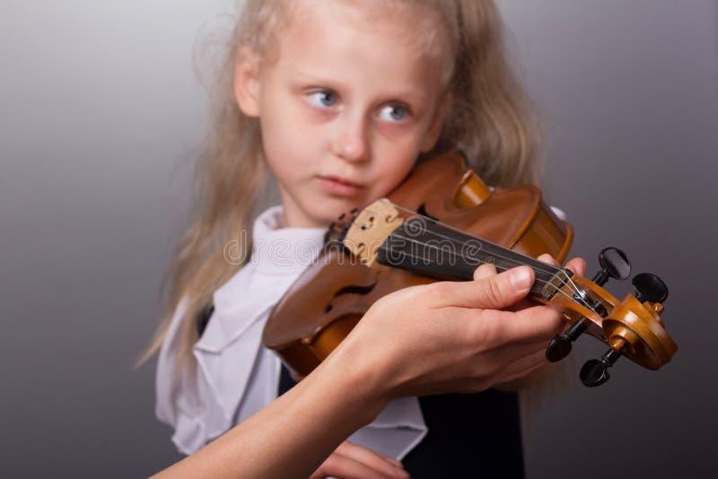La mano de la maestra ayuda a una niña a tocar el violín foto de archivo