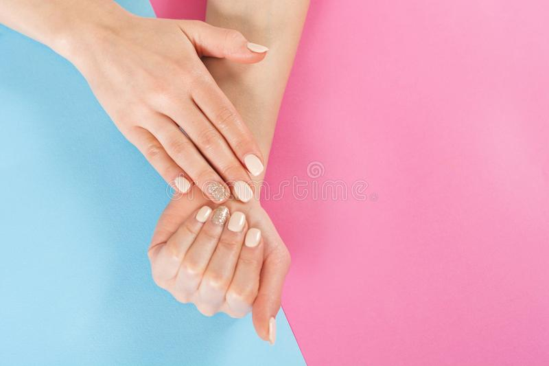 La mano de la muchacha de la belleza con los clavos manicure en fondo azul y rosado imagenes de archivo
