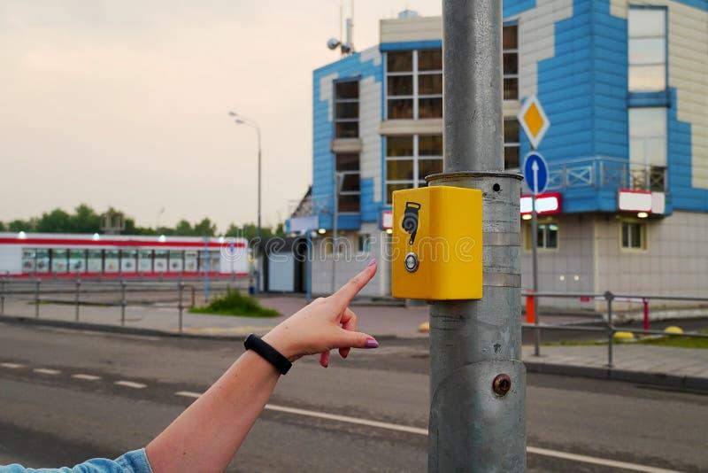 La mano de la muchacha presiona el botón del paso de peatones Paso de peatones electrónico del botón amarillo Una muestra de la m foto de archivo