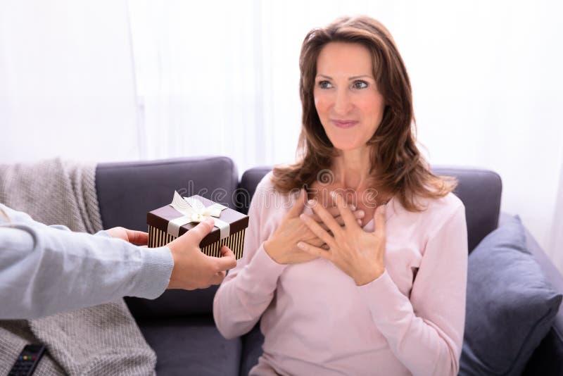 La mano de la muchacha que da el regalo de cumplea?os a su madre fotos de archivo libres de regalías