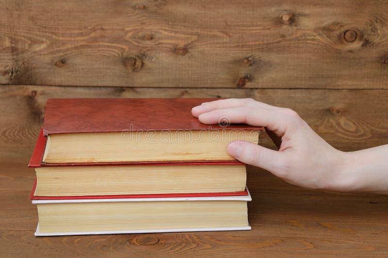 La mano de la muchacha toma un libro viejo en un fondo marrón de madera imágenes de archivo libres de regalías