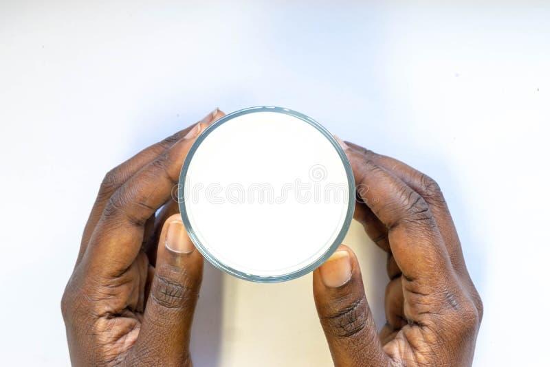La mano de la mujer africana que sostiene el vidrio de leche fresca caliente en el fondo blanco Comida y bebida de la visión supe imagen de archivo
