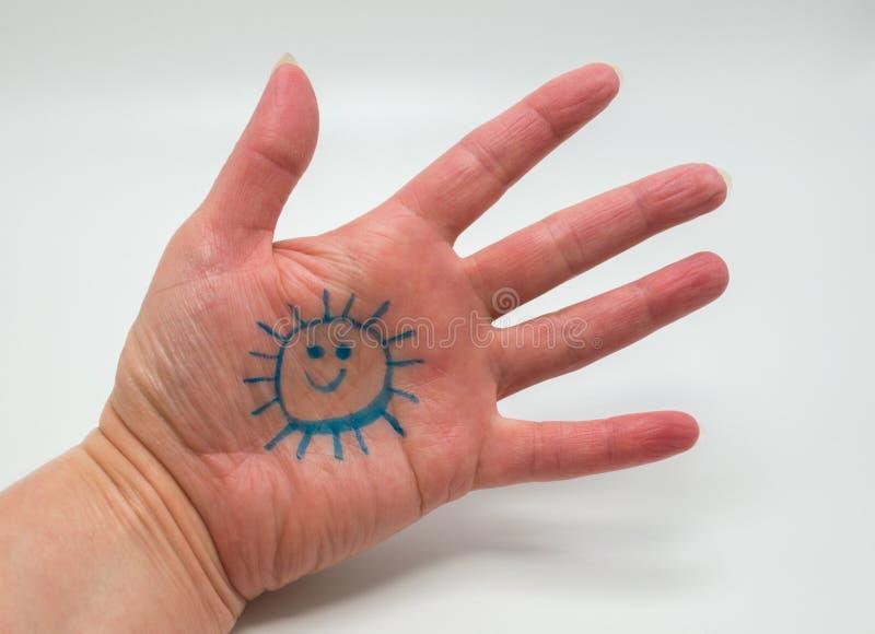 La mano de la mujer con la cara sonriente de la sol dibujada en la palma aislada en blanco fotografía de archivo