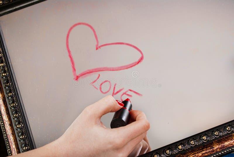 La mano de la mujer con el corazón rojo del dibujo del lápiz labial y la palabra aman en el espejo para el día de tarjetas del dí fotos de archivo