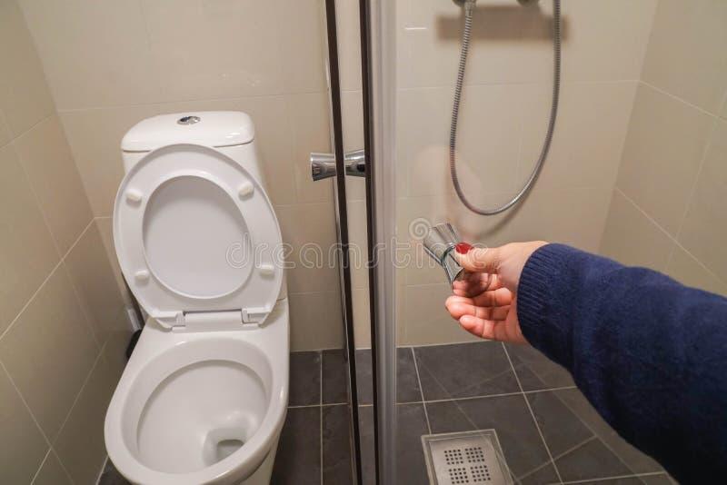 La mano de la mujer con el suéter azul marino abre el armario de cristal de la cabina de la ducha en cuarto de baño foto de archivo
