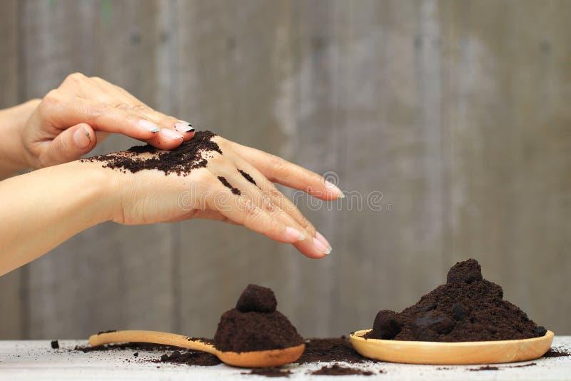 La mano de la mujer con friega los argumentos de caf? en fondo de madera, belleza y concepto sano del cuidado imagen de archivo libre de regalías