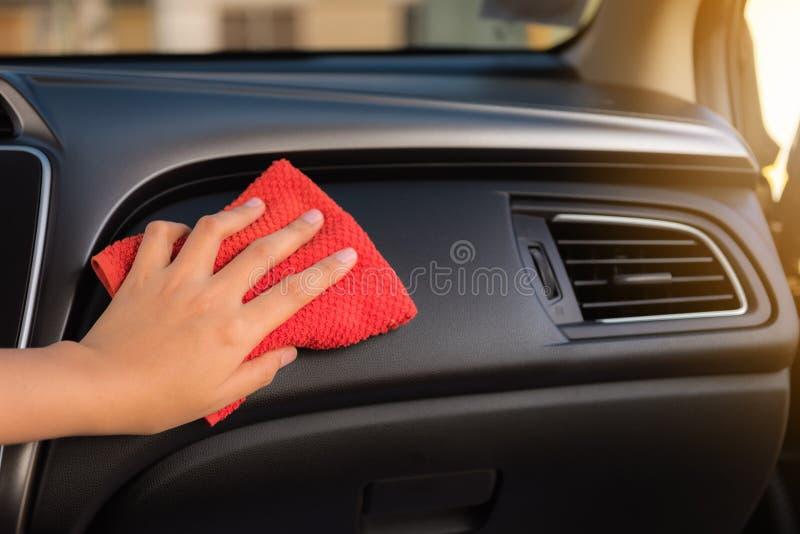 La mano de la mujer del primer está limpiando su consola del coche con la microfibra t foto de archivo libre de regalías